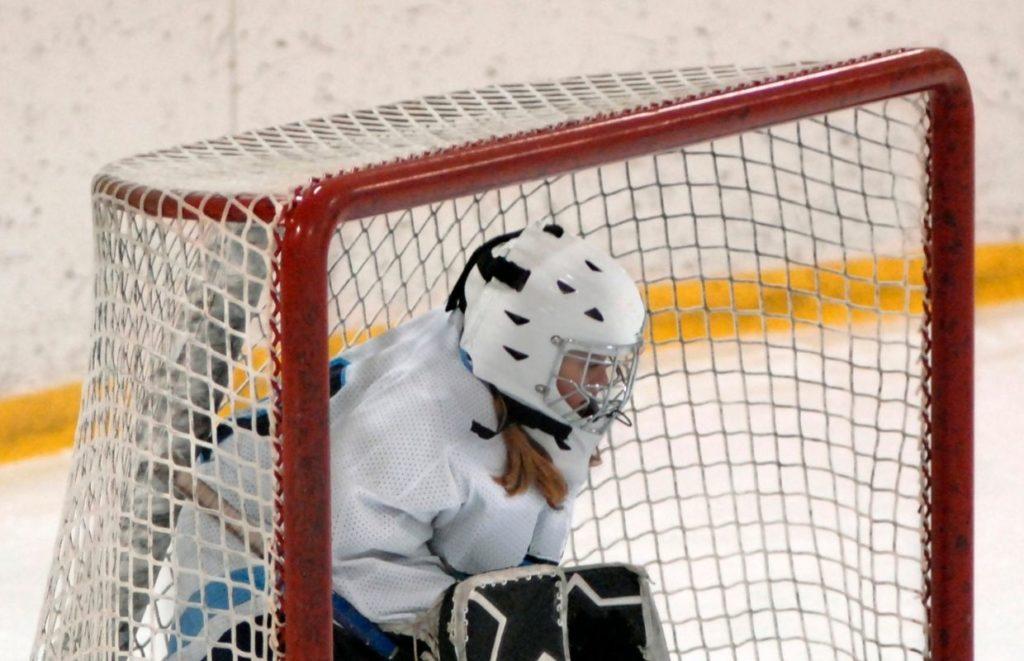 A hockey goalkeeper wearing a white goalie helmet