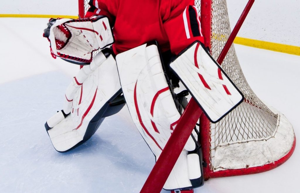 Red and white ice hockey goalie protective pads