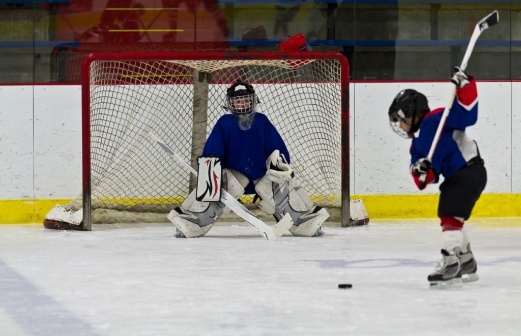 Kid practising shooting an ice hockey puck with a goalie