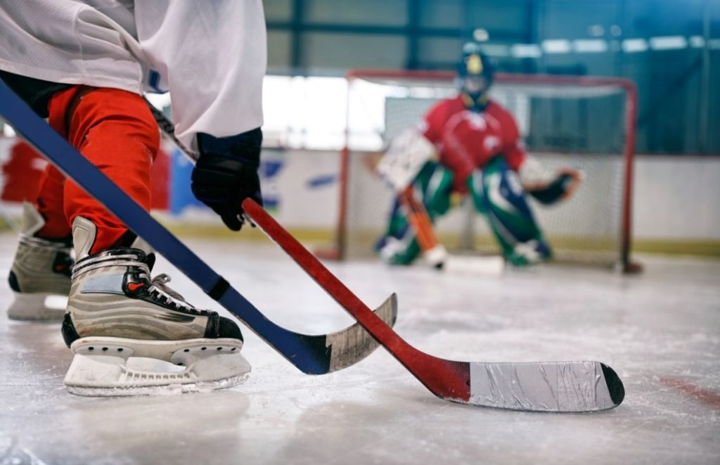 A kid with a wrapped up hockey stick taking a shot on goal