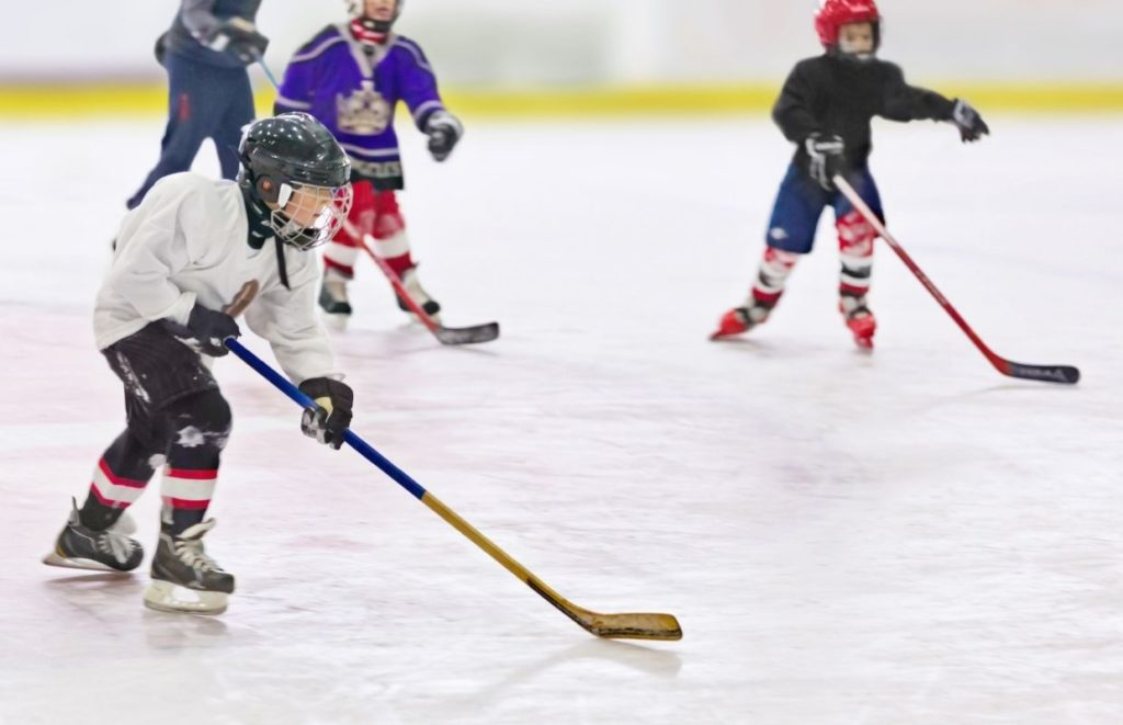 Young children playing ice hockey for a team