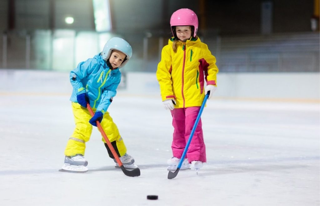 At What Age Should Kids Start Hockey - two kids learning to play ice hockey